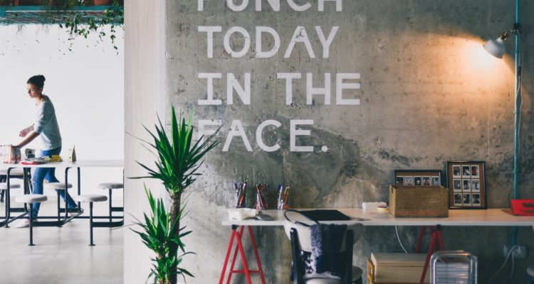 inspiration to combat performance anxiety at work. A fun wall display in a co-working space that says punch today in the face.